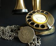 Antique Phone & Coin. A Photo of two antiques - a phone & a silver chain with a coin, used a women waist belt Royalty Free Stock Photography
