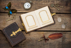 Antique photo album with butterfly over wooden background Stock Photos