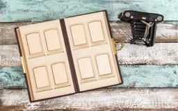 Antique photo camera photo album pictures wooden background. Antique photo camera and photo album for pictures on wooden background royalty free stock image