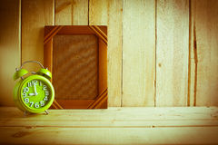 Antique photo frame and clock on wooden table over wood background Stock Photos
