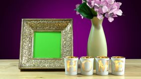 Antique photo frame with green screen and burning home candles. Stock Photography