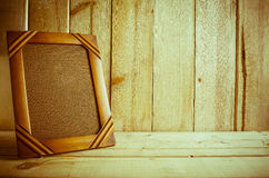 Antique photo frame on wooden table over wood background Royalty Free Stock Photos