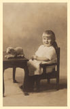 Antique photograph of a baby girl. Original antique photograph portrait of a baby girl sitting next to a table with a stuffed animal.  Taken in 1920 Royalty Free Stock Photography
