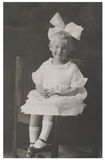 Antique photograph girl with big bow. Antique portrait photograph of a young girl in a white dress, wearing a big bow in her hair.  Taken in 1923 Stock Photography