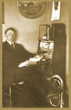 Antique photograph of man at desk. Original antique photograph portrait of a man sitting at a desk with books and papers, with part of a tube in the foreground Stock Photos