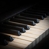Antique piano keyboard fading into a black background with copy Stock Photo