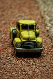 Antique pick-up car miniature. On dirty street Royalty Free Stock Photography