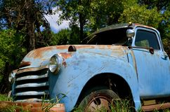 Antique Pickup Parked in the Long Grass. A very faded blue pickup is parked in the long grass near a wood Stock Images