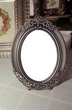 Antique picture frame. An antique tin/pewter picture frame with blank oval center for future image placement Royalty Free Stock Images