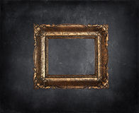 Antique picture frame on black grunge wall. Empty antique picture frame on black grunge wall Stock Image