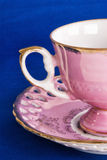 Antique Pink Cup and Saucer on Blue Textured Background Stock Image