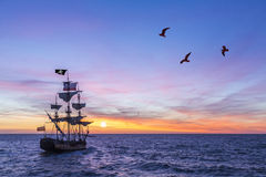Antique Pirate Ship. Pirate Ship leaving the harbor at the sunset for a long campaign against the loyal marines Royalty Free Stock Image