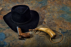 Antique pistol and powder horn with cowboy hat on slate Stock Images