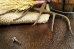 Antique pitchfork and forget iron nail on burlap closeup. Antique pitchfork and forged nail on burlap sack against rural brick wall with whole wheat Stock Images