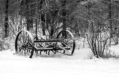 Antique Plow in Snow. Antique farmers plow in snow next to woods Stock Images