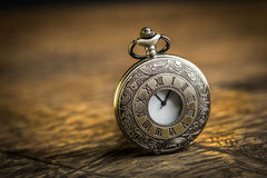 Antique pocket watch. Vintage Antique pocket watch on grunge wooden background Royalty Free Stock Photography