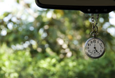 Antique pocket watch. Hanging from mirror showing five o'clock Stock Image
