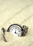 Antique pocket watch buried in sand Royalty Free Stock Image