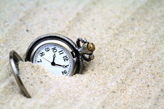 Antique pocket watch buried in sand Stock Image