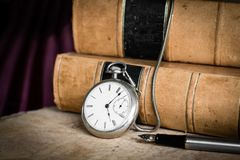 Antique pocket watch on burled wood with old leather bound books and fountain pen royalty free stock images