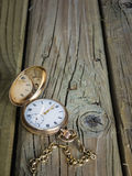 Antique pocket watch  and fob chain on aged wooden boards Stock Photo