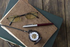 An antique pocket watch, glasses and books Stock Photos