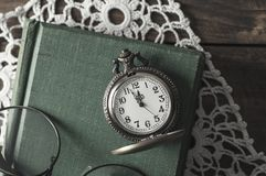 An antique pocket watch, glasses and books Royalty Free Stock Photos