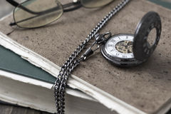 An antique pocket watch, glasses and books Royalty Free Stock Images