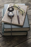 An antique pocket watch, glasses and books Royalty Free Stock Photo