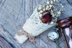 Antique pocket watch and hourglass with dried flowers. Stock Image