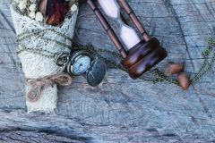 Antique pocket watch and hourglass with dried flowers. Royalty Free Stock Photography