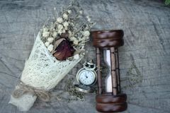 Antique pocket watch and hourglass with dried flowers. Royalty Free Stock Images