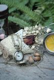Antique pocket watch and hourglass with dried flowers. Royalty Free Stock Photo