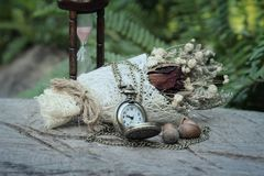Antique pocket watch and hourglass with dried flowers. Stock Images