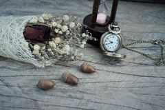 Antique pocket watch and hourglass with dried flowers. Royalty Free Stock Image