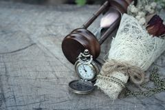 Antique pocket watch and hourglass with dried flowers. Stock Photography