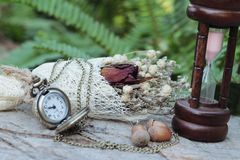 Antique pocket watch and hourglass with dried flowers. Stock Photos