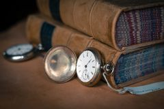 Antique pocket watch on leather with old books royalty free stock photos