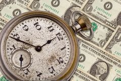 Antique pocket watch and money. Antique pocket watch clock face on top of money isolated on white with a clipping path Stock Image