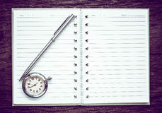 Antique pocket watch on notebook for notes, On old textured wood. stock photos