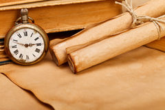 Antique pocket watch and paper rolls Royalty Free Stock Photos