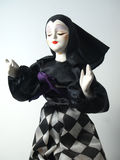 Antique porcelain doll. Porcelain doll in black and white checkered skirt with black hat on white Royalty Free Stock Photography