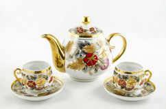 Antique porcelain tea and coffee set. Beautiful porcelain coffe and tea set with handmade floral motif. Contains two cups and jug royalty free stock photos