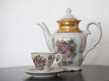 Antique porcelain teapot with cup and saucer. On wooden table Royalty Free Stock Photography