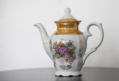 Antique porcelain teapot with flower print. On wooden table Royalty Free Stock Image