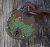 Antique portable metal padlock on wooden door. Antique portable padlock made from metal on wooden door royalty free stock images