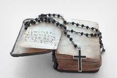 Antique prayer-book and a black rosary on it Stock Images