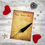Vintage Valentine`s Day card with red cuddle hearts, wooden decorations, ink and quill - top view stock images