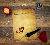 Vintage Valentine`s Day card with red cuddle heart, wooden decorations, painted hart, red candle and ink and quill on antique oak royalty free stock photo