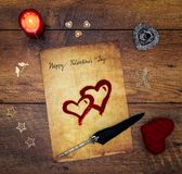 Vintage Valentine`s Day card with red cuddle heart, wooden decorations, painted hart, red candle and ink and quill on vintage oak royalty free stock image
